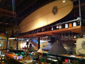 Surfboards hang above the center bar at Longboards