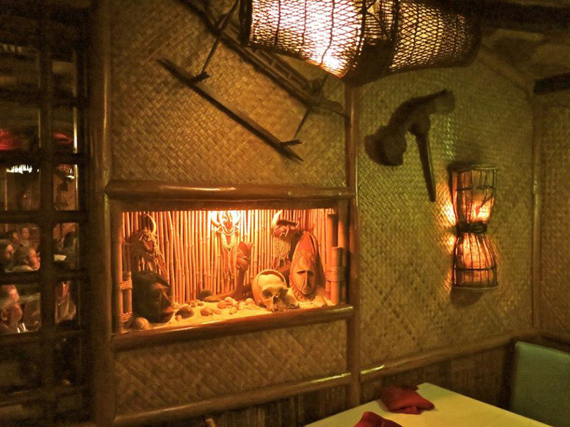 One of the shadow boxes in the Samoa room at The Mai-Kai that contains art pieces including shrunken skulls. (Photo by Sven Kirsten, December 2016)