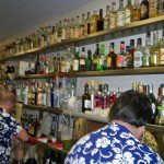 Bartenders work The Mai-Kai's kitchen service bar. The top shelf contains rare and collectible rums that date back more than 50 years. (Stop 5)