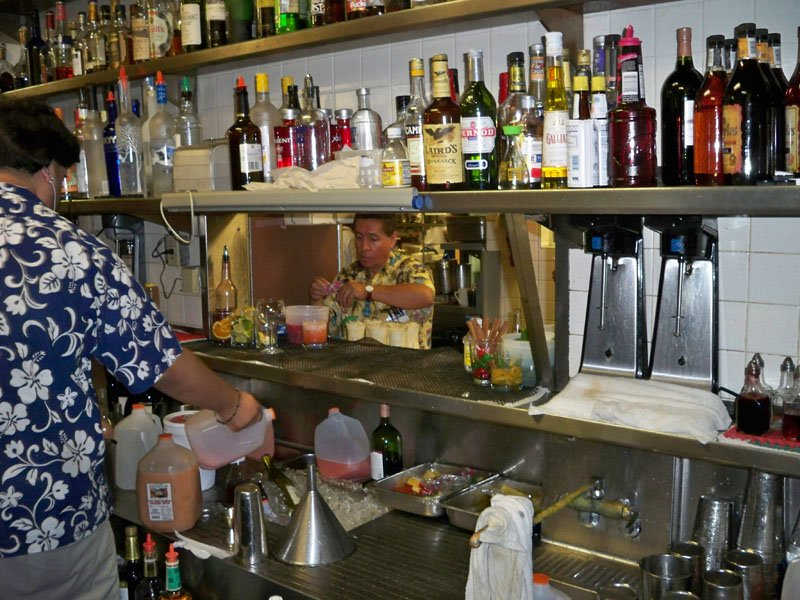 Bartenders mix in The Mai-Kai's kitchen service bar while a waiter garnishes drinks before serving them to dining room customers. (Stop 5)