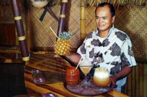 A postcard shows a server in the early years of The Molokai bar holding the welcoming Piña Passion. (MaiKaiHistory.com)