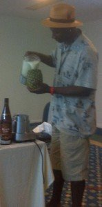 Ian Burrell pours Pina Coladas into pineapples for seminar participants to sample
