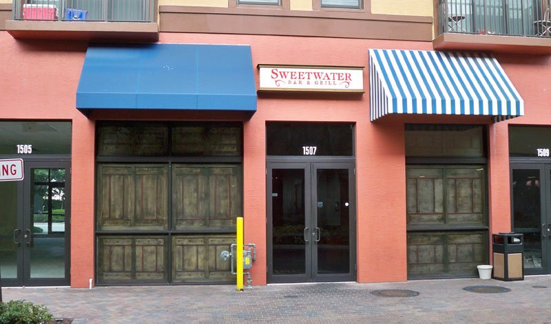 The rear entrance to Sweetwater Bar & Grill with empty storefronts on either side and apartments above.