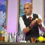 Mixologist Freddy Diaz demonstrates how to flame an orange peel to give a drink the essence of fruit