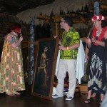 "A vintage painting of Mai-Kai owner Mireille Thornton (right) is introduced by The Hukilau organizer Christie ""Tiki Kiliki"" White. It was restored and presented by Tim ""Swanky"" Glazner (center)."