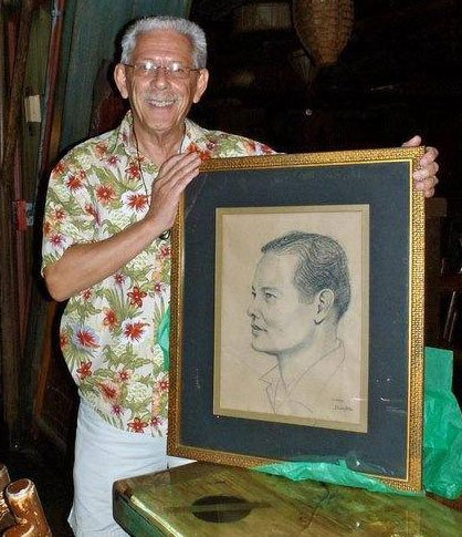 Ron Licudine holds a portrait of his father, Mariano, The Mai-Kai's original mixologist from 1956 until his retirement in 1979