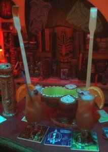 A pair of Backscratchers are surrounded by some Enchanted Tiki Room 50th anniversary collectibles at The Atomic Grog