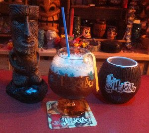 The Hukilau's 10th anniversary snifter glass from 2011 is flanked by last year's official mug by Tiki Diablo and 2013 coconut mug by Eeekum Bookum. The snifter contains The Atomic Grog's updated tribute to The Mai-Kai's Black Magic