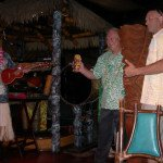 Artist Jeff Chouinard (right) presents a tiki he carved for The Mai-Kai to owner Dave Levy and manager Kern Mattei (as King Kukulele) during Saturday night's Main Event during The Hukilau 2014.