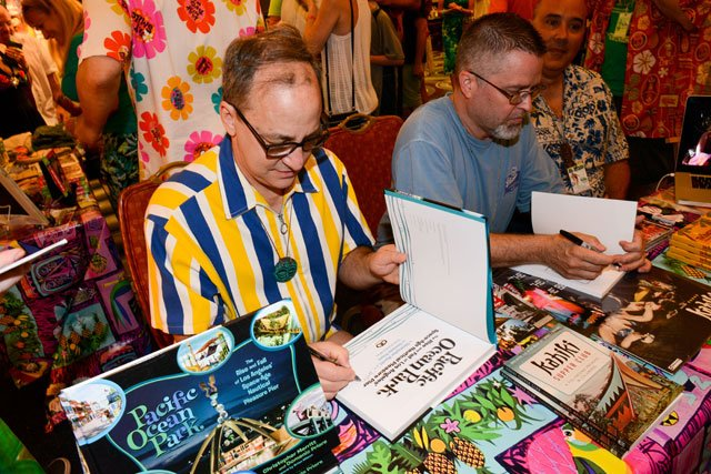 Authors Domenic Priore (left) and Jeff Chenault sign copies of their books, which were also the subject of symposiums at The Hukilau. (Photo by Go11Events.com)
