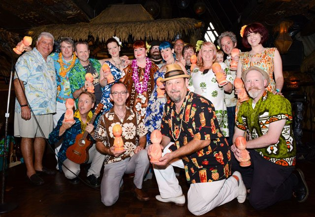 "During stage presentations before the dinner show, The Hukilau's Christie ""Tiki Kiliki"" White (center) poses with her partners, staff and crew after presenting them with special versions of the 2015 event mug by Tiki Diablo. (Photo by Go11Events.com)"