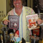 Mixologist and author Warren Bobrow, representing Stroh, shows off some of his books.
