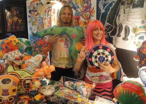 Harold Golen helps pop artist Valentina of Kawaii Universe show off her colorful designs in his gallery booth. (Photo by The Atomic Grog)