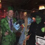The Evil Monkey and Wicked Witch accept their best costume award and prizes from The Mai-Kai's Kern Mattei (aka Elvis), The Atomic Grog's Hurricane Hayward (The Tiki Riddler), and The Mai-Kai's Pia Dahlquist (the kooky clown).