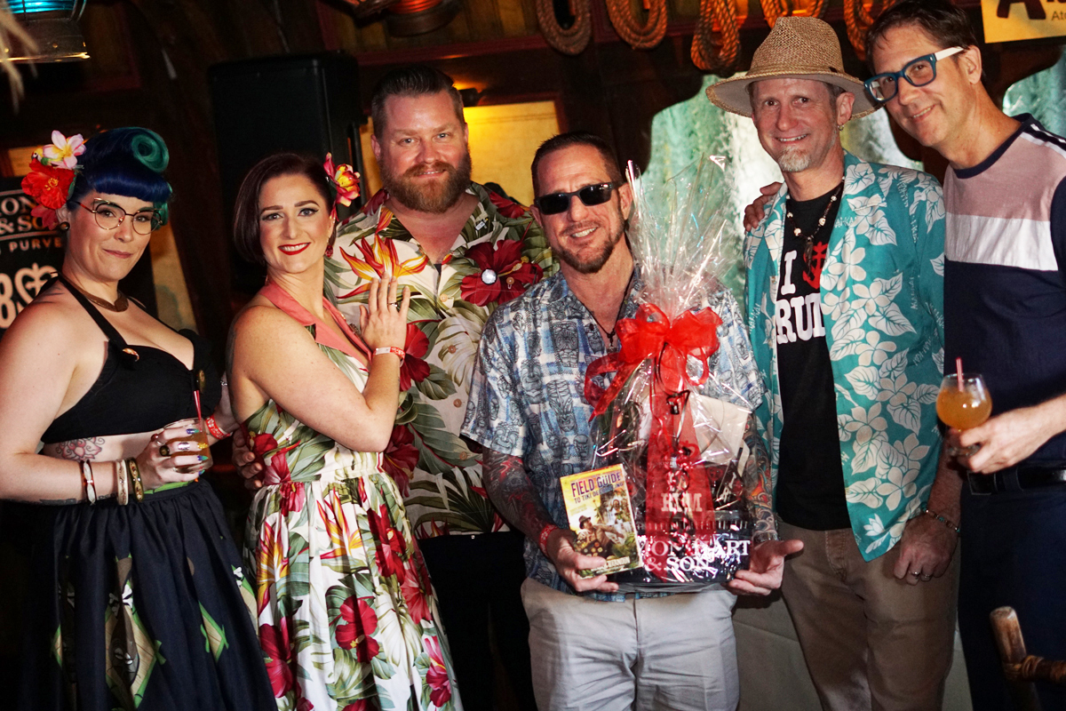 Event organizers (from left) Jupiter Jones, Kari Ryan and Typhoon Tommy present a bottle of Lemon Hart's new Blackpool spiced rum to the raffle winner with assistance from Hurricane Hayward and Skinny Jimmy Stingray (right)