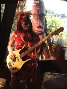 Bassist Sarah Butler of The Surfrajettes is guarded by one of The Mai-Kai's many tikis during the band's performance in The Molokai bar during The Hukilau 2017