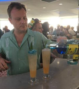 """Stuart Hudson of Trailer Happiness puts the finishing touch on the Cotton Mouth Killer during the Tiki Tower Takeover at The Hukilau 2018. The London bar adds blue food coloring to Wray & Newphew Overproof rum to create its signature """"Bluberproof."""" (Photo by Hurricane Hayward)"""