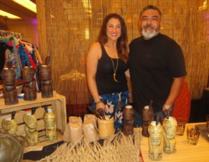 Tiki Diablo, with wife Stephanie Mehr, shows off his mugs in the Tiki Treasures Bazaar at The Hukilau 2016. (Photo by Hurricane Hayward)