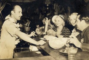 Donn Beach serves guests at his first bar in Hollywood, circa late 1930s. Note in the foreground: The Pearl Diver cocktail in its vintage glass. The Mai-Kai serves its version, the Deep Sea Diver, in the same glass, resurrected in 2015 by Beachbum Berry and Cocktail Kingdom