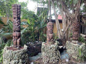 A trio of Tikis created by Florida artists Will Anders, Tom Fowner and Jeff Chouinard greets guests at the entrance to The Mai-Kai. (Photo by Hurricane Hayward, September 2021)